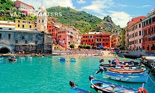 Photograph of Portofino, Italy from the marina. The water is turquoise, and there are boats in the marina. Yacht charter italy is popular here.