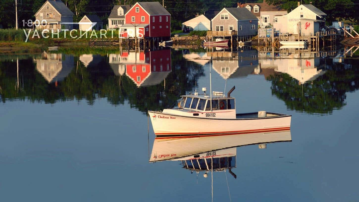 Photograph of a marina in Kennebunkport, ME. There is 1 small boat anchored in the calm water. The water looks like glass. Perfect reflection. The marina is surrounded by cute little buildings. One has a big lobster painted on the side in red.