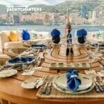 Photo taken from the back entrance of a yacht toward the back of the yacht. The yacht is facing away from a gorgeous Mediterranean cityscape. There is a table in the foreground that is elegantly set. It features blue, white, and beige. It is a large table on the deck of a yacht.