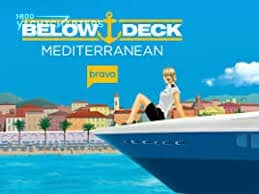 Profile photograph of the pointed front of a motoryacht, with a woman sitting on it. She has blonde pulled back hair. The Below Deck Mediterranean bravo TV series logo is over the top of the photo. There are colorful homes in the background, as if a seaside village.