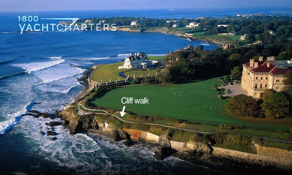 Aerial photograph of the Newport Cliff Walk next to mansions on the coastline. The water laps at the cliffs on the left side of the photo.