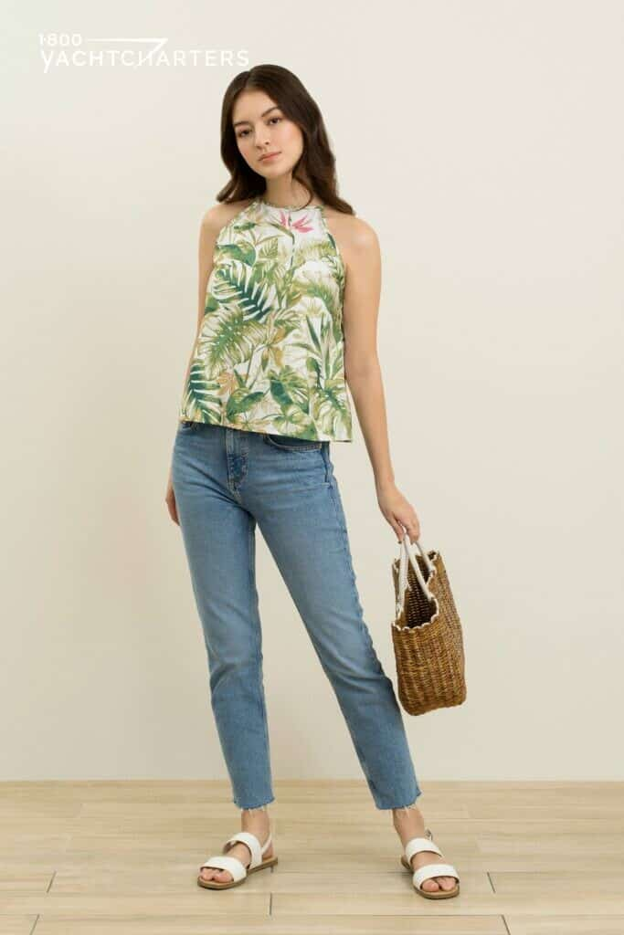 Photograph of a dark-haired girl standing and facing the camera. She is wearing blue denim jeans and a tropical tank top with green palm leaves on it. She is holding a red purse with beige straps in her left hand. Her right arm is by her side.