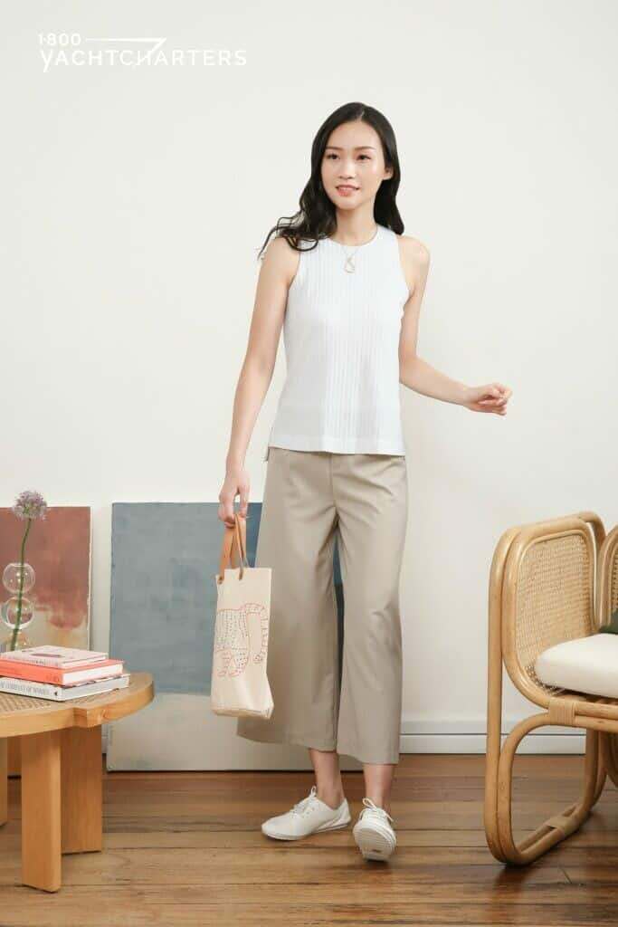 Photograph of a dark-haired girl wearing khaki-colored culottes and a white sleeveless top. She is facing the camera. She is wearing white sneakers. She is carrying a beige flat tote bag with a cat drawing on it in her right hand, and she has nothing in her left hand. There is a rattan chair with white cushion on her left side, and there is a wooden table on her right side. There are 2 books on the table, as well as a bud vase with a single thistle-like grey flower stem in it. There is a beige wall behind her. There are paintings propped against the wall on the floor on her right side.