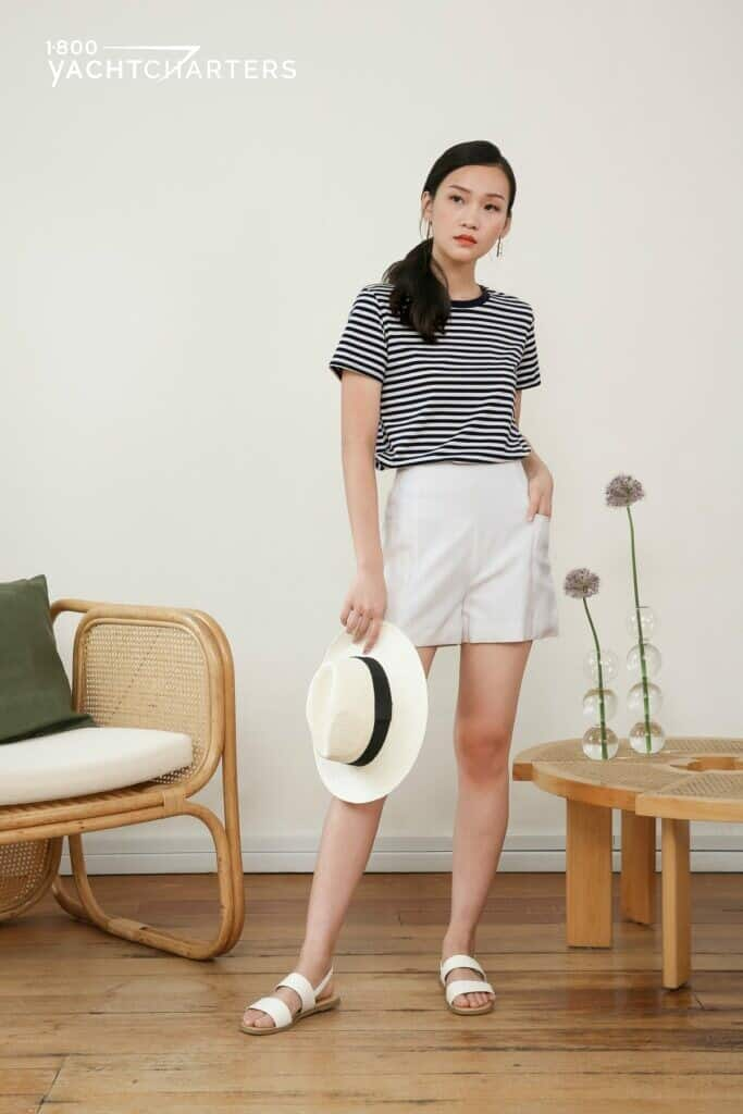 Photograph of an Asian girl in nautical striped short sleeved shirt with white side-pocket shorts. She is facing the camera. The photo includes the top of her head down to her feet. She is wearing white flat sandals. She is holding a white bowler hat with black band in her right hand. Her left hand is on her left hip. She is looking toward the left side of the photograph. There is a rattan chair with white cushion on it beside her on her right side, and a small wooden table on her left side. The table has 2 bud vases on it with flower stems and 1 grey thistle-like flower in each.