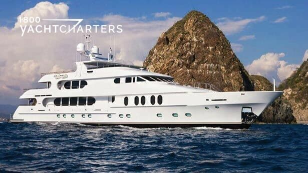 Profile photograph of motoryacht LADY JANET. There is a tall, triangular-shaped rock in the background. The yacht is underway, and is headed toward the center of the right side of the photo