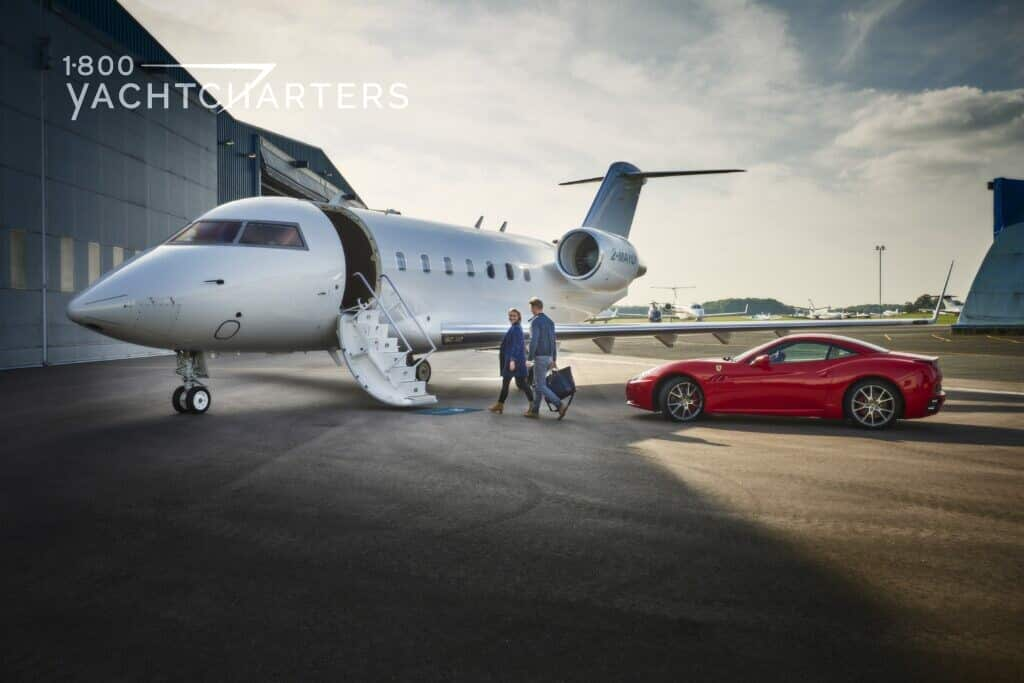 Photograph of a private jet with a red ferrari next to it. The jet is on the tarmac. The jet door is open, and the stairs are deployed. 2 men are walking up to the jet.