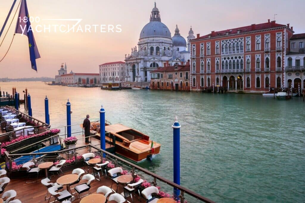 Photograph of a Venice canal lined with boats on the front side and ornate hotels on the back side